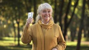 Mujer mayor sonriente que presenta la pila de billetes de dólar en parque, retiro previsto foto de archivo libre de regalías