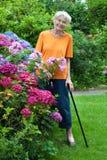 Mujer mayor sonriente que se coloca en el jardín de flores imagen de archivo