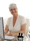 Mujer mayor sonriente que trabaja con un ordenador Fotografía de archivo
