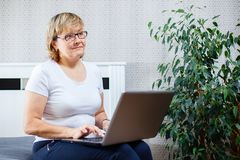 Mujer mayor sonriente que trabaja en el ordenador portátil en casa Imágenes de archivo libres de regalías