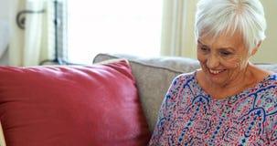 Mujer mayor sonriente que usa el ordenador portátil en sala de estar almacen de video