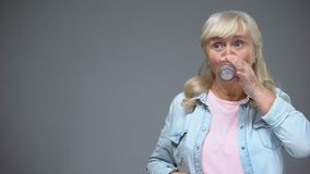 Mujer mayor sorprendida con el gusto de la píldora que lo toma con el alivio, atención sanitaria metrajes