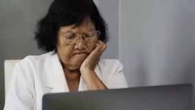 Mujer mayor subrayada que trabaja en el ordenador portátil almacen de metraje de vídeo