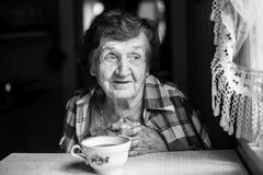 Mujer mayor, té de consumición que se sienta en la tabla en la casa Fotografía de archivo