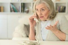 Mujer mayor trastornada con el teléfono imágenes de archivo libres de regalías