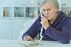 Mujer mayor trastornada con el teléfono imagen de archivo