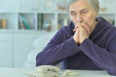 Mujer mayor trastornada con el teléfono foto de archivo libre de regalías