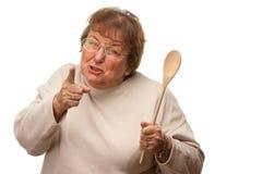 Mujer mayor trastornada con la cuchara de madera Fotos de archivo