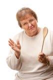 Mujer mayor trastornada con la cuchara de madera Imágenes de archivo libres de regalías