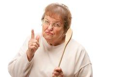 Mujer mayor trastornada con la cuchara de madera Imagen de archivo