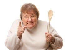 Mujer mayor trastornada con la cuchara de madera Imagenes de archivo