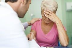 Mujer mayor triste con el doctor Imagen de archivo libre de regalías