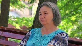 Mujer mayor triste en el parque almacen de metraje de vídeo