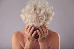 Mujer mayor triste en fondo gris Fotografía de archivo