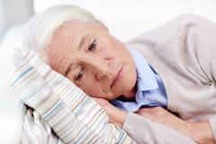 Mujer mayor triste que miente en la almohada en casa Fotos de archivo libres de regalías