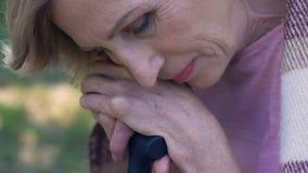 Mujer mayor triste que se sienta en parque con el bastón, sintiendo solo e infeliz almacen de video