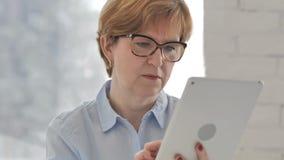 Mujer mayor usando la tableta para Internet de la ojeada almacen de metraje de vídeo