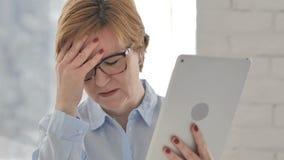 Mujer mayor usando la tableta y el reaccionar al fracaso del proyecto almacen de metraje de vídeo
