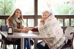 Mujer mayor y cuidador joven que se sientan en la tabla Imagenes de archivo