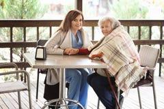 Mujer mayor y cuidador joven que se sientan en la tabla Fotografía de archivo libre de regalías