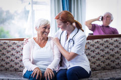 Mujer mayor y doctor de sexo femenino que obran recíprocamente en sala de estar Imagen de archivo libre de regalías