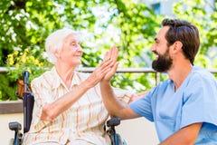 Mujer mayor y enfermera que dan el alto cinco foto de archivo
