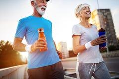 Mujer mayor y hombre que corren haciendo ejercicios de la aptitud fotos de archivo libres de regalías