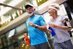 Mujer mayor y hombre que corren haciendo ejercicios de la aptitud imagenes de archivo