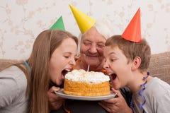Mujer mayor y sus nietos con la torta de cumpleaños Fotos de archivo