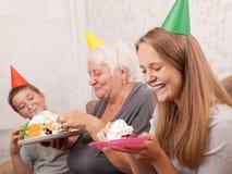 Mujer mayor y sus nietos con la torta de cumpleaños Imagenes de archivo