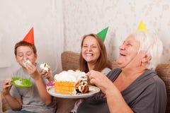 Mujer mayor y sus nietos con la torta de cumpleaños Imagen de archivo