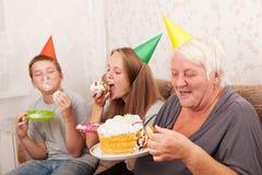 Mujer mayor y sus nietos con la torta de cumpleaños Foto de archivo libre de regalías