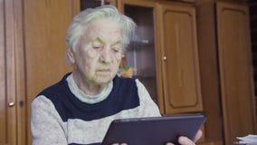 Mujer mayor y tableta electrónica metrajes
