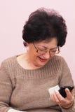 Mujer mayor y teléfono de Smart. Foto de archivo libre de regalías
