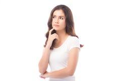 Mujer a medias asiática que piensa en el fondo blanco Imagen de archivo libre de regalías