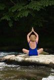 Mujer meditating con yoga en una roca plana del río. Fotos de archivo libres de regalías