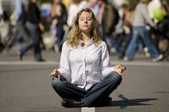 Mujer meditating en calle urbana ocupada Imágenes de archivo libres de regalías