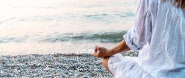 Mujer meditating en el mar foto de archivo libre de regalías