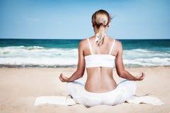 Mujer meditating en la playa Fotos de archivo
