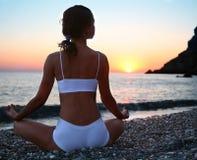 Mujer meditating en la playa Fotografía de archivo