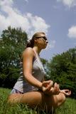 Mujer meditating en parque imagen de archivo libre de regalías