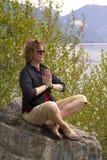 Mujer meditating en un lago Imagenes de archivo