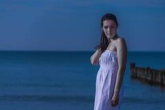 Mujer meditativa hermosa en una costa iluminada por la luna Fotografía de archivo libre de regalías