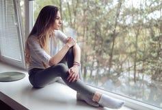 Mujer melancólica que se sienta en la repisa de la ventana en casa Fotos de archivo