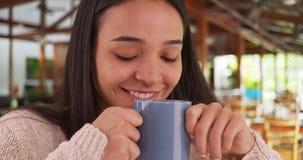 Mujer mexicana que se sienta en café con una taza de café agradable Fotos de archivo