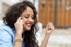 Mujer mezclada hermosa en fondo urbano en el teléfono Foto de archivo libre de regalías