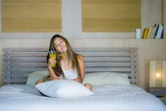 Mujer mezclada latina asiática hermosa y feliz atractiva joven que miente en el dormitorio de la cama en casa que bebe el zumo de imagenes de archivo