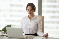 Mujer milenaria atenta que medita en oficina para reducir el str del trabajo foto de archivo