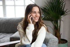 Mujer milenaria sonriente del mestizo que habla en el teléfono en casa Foto de archivo libre de regalías