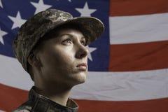 Mujer militar delante de la bandera de los E.E.U.U., mujer militar vertical delante de la bandera de los E.E.U.U., horizontal Imagen de archivo libre de regalías